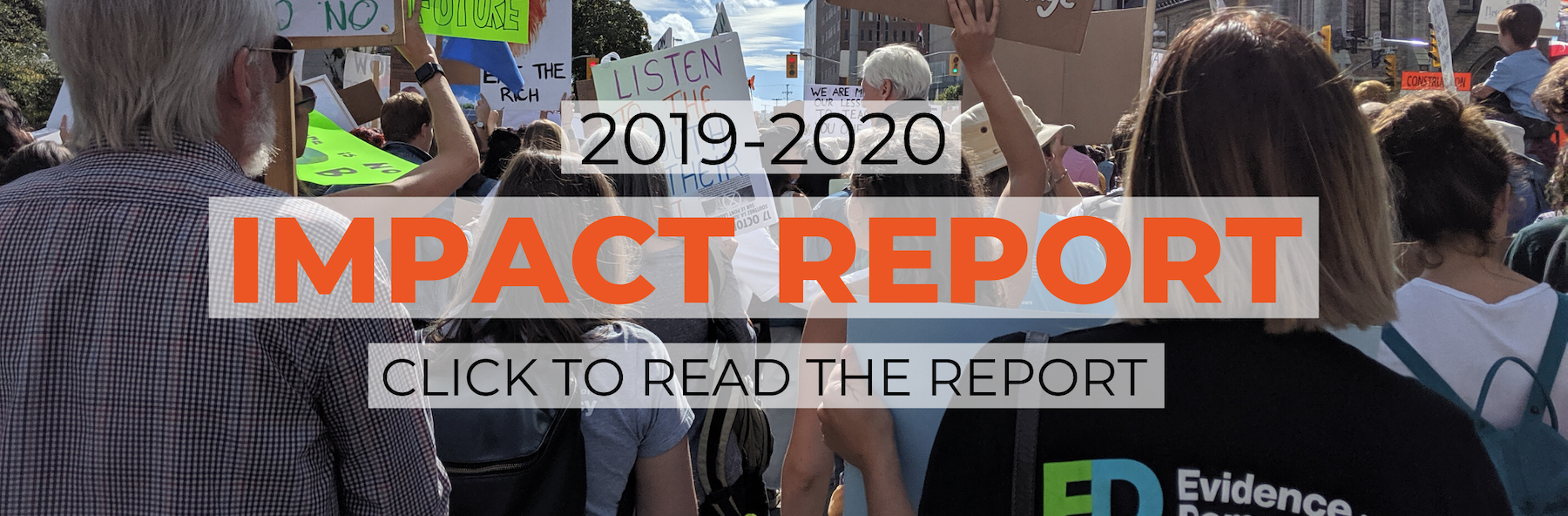 "The words ""2019-2020 Impact Report. Click to read report"" in black and orange lettering displayed over an image of a crowd at a climate protest with an E4D staff member facing away from the camera wearing an Evidence for Democracy tshirt."