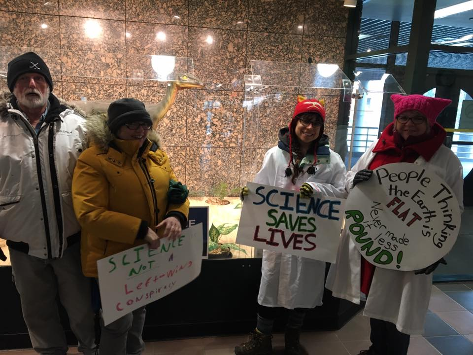 "Four people in winter coats holding signs reading ""science saves lives"" and ""people thinking the earth is flat never made it less round"""