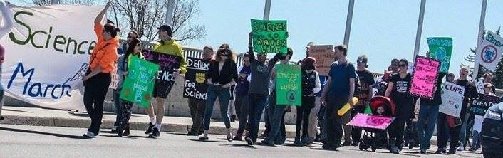 "Marchers on a sidewalk with a banner reading ""Science March"" and a variety of signs"